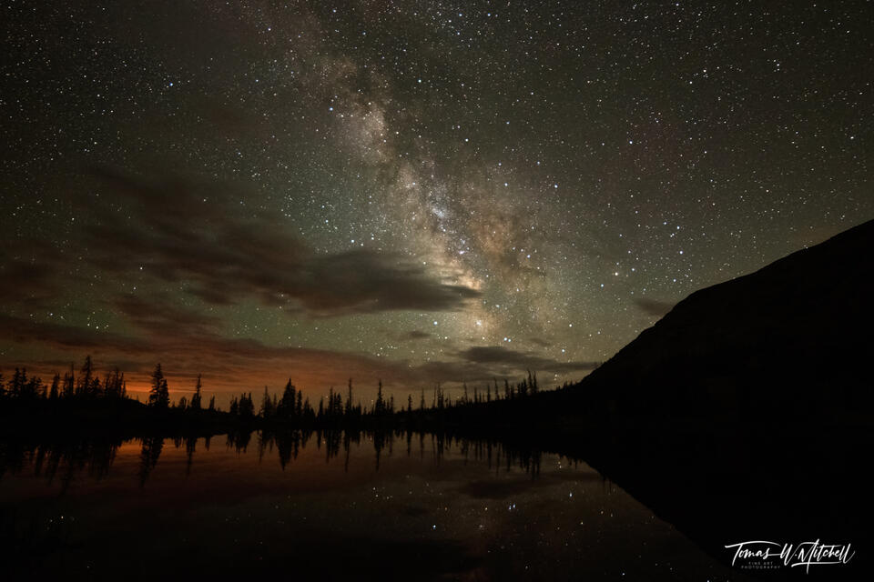 Framed photograph of milky way galaxy over mountain lake.